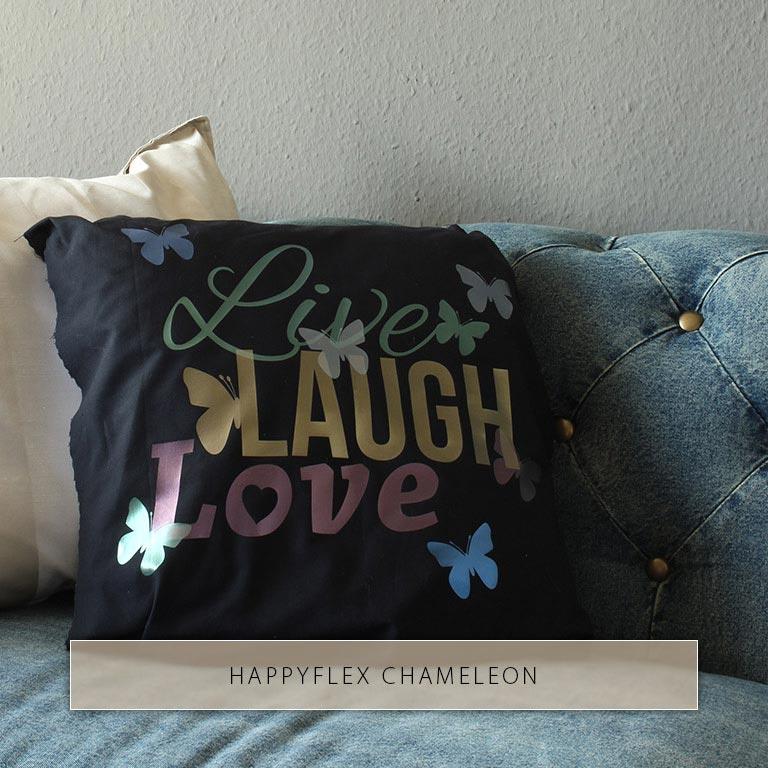 Live Laugh Love et des papillons avec l'éclat métallique de différents films de repassage caméléon sur un oreiller noir.