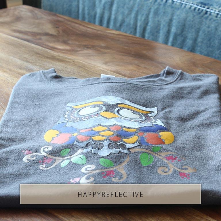Hibou coloré avec des éléments réfléchissants imprimés sur le T-shirt.